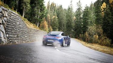 Porsche 911 Carrera 4S drifting on wet hairpin bend