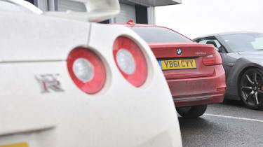 BMW 320d rear badge, with Nissan GT-R at Bedford Autodrome